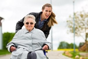 smiling woman in wheelchair being pushed by smiling woman