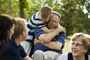 man in wheelchair and child hugging in group