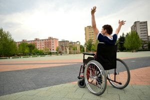 man in wheelchair with both arms raised in the air