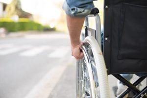 close up of wheelchair wheel with man's hand on it