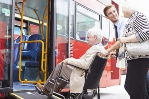 man in wheelchair being pushed up ramp on bus