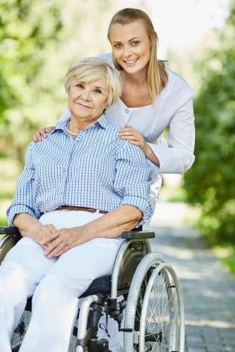 smiling woman in wheelchair with smiling woman standing behind her
