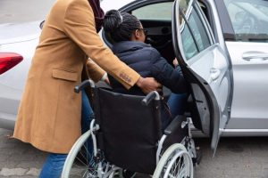 woman in wheelchair being helped into backseat of car