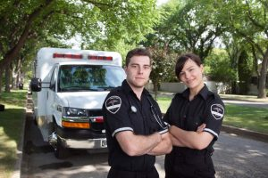 male and female paramedics standing in front of ambulance