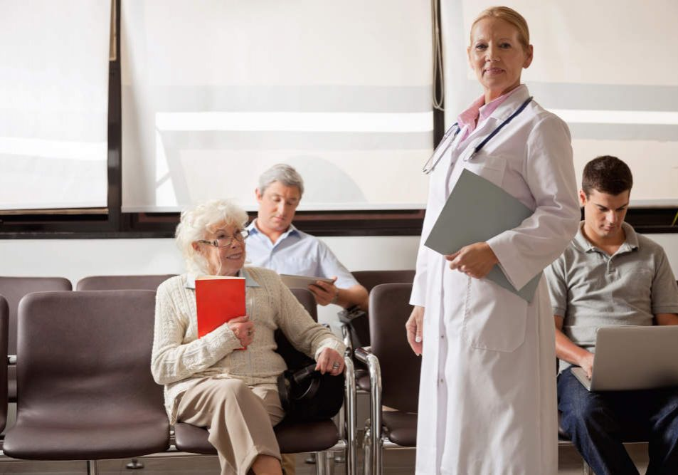 Portrait of female doctor holding file while people sitting in hospital lobby