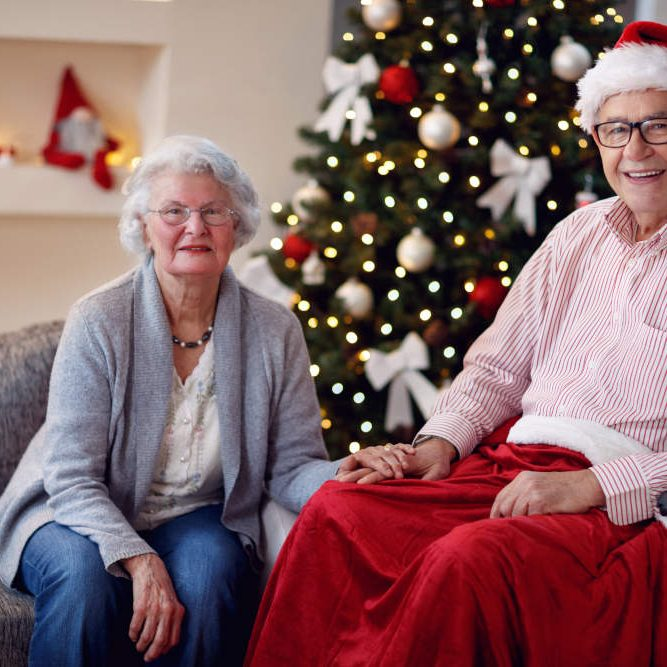 man sitting in wheelchair with santa hat on with woman sitting on sofa next to him