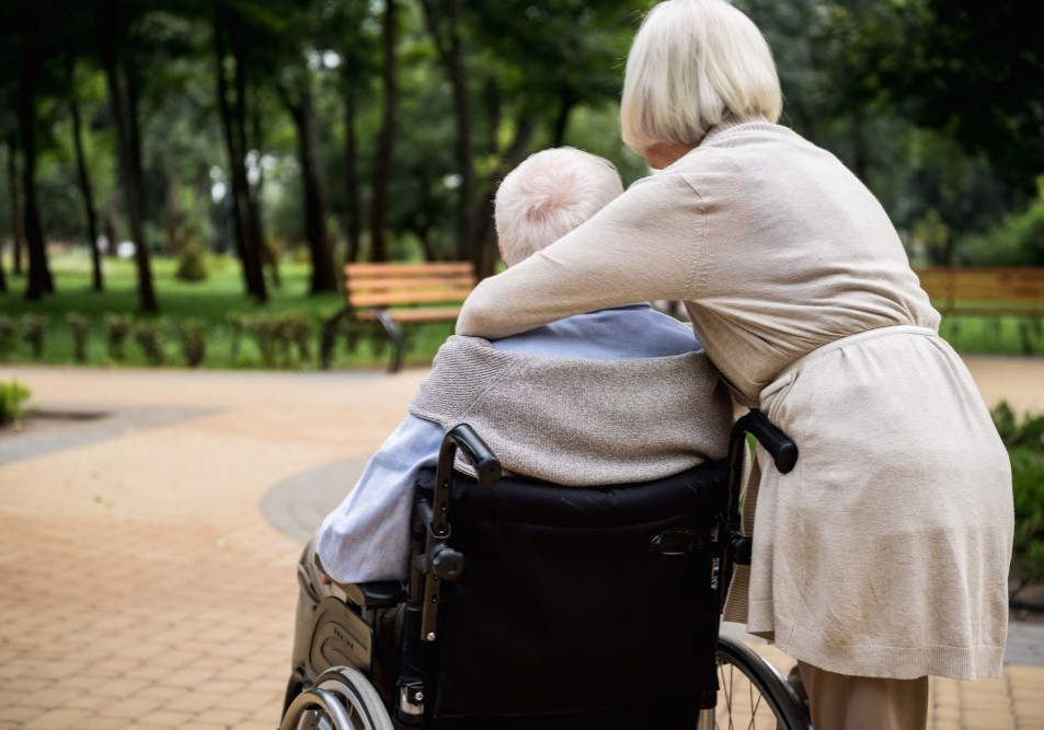 Lady hugging man sitting in wheelchair