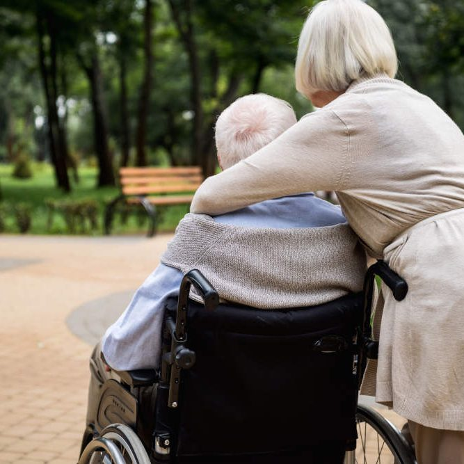 Lady hugging man sitting in wheelchair