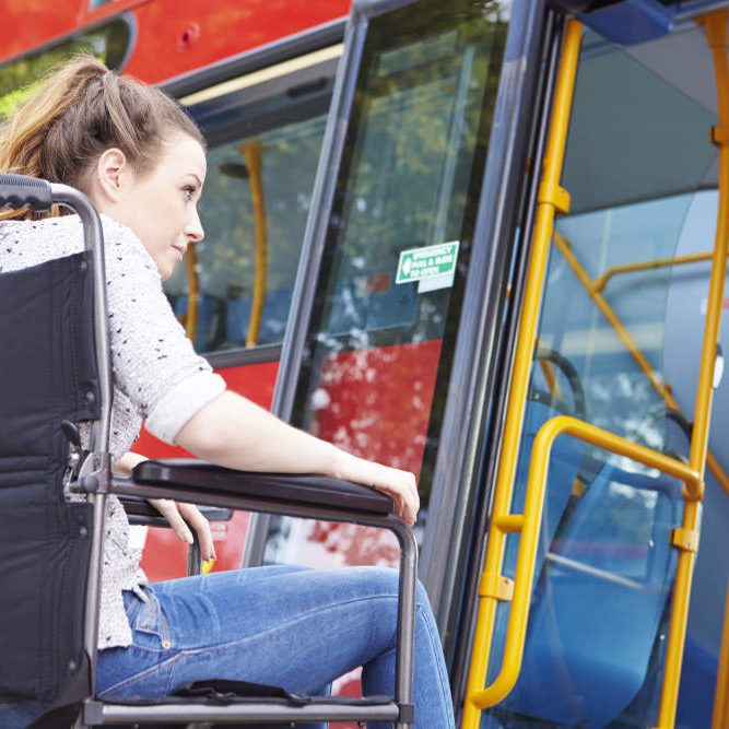woman in wheelchair sitting in front of open bus door
