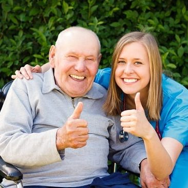 smiling man in wheelchair with female smiling nurse both giving thumbs up