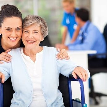 smiling woman in wheelchair and woman behind her also smiling