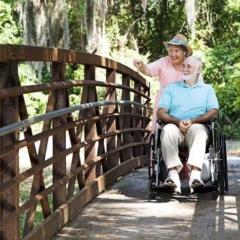smiling woman pushes smiling man in wheelchair across wooden bridge